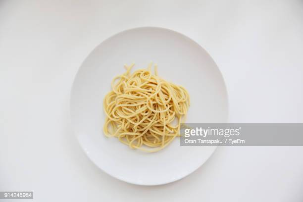 directly above shot of spaghetti in plate over white background - pasta stock pictures, royalty-free photos & images