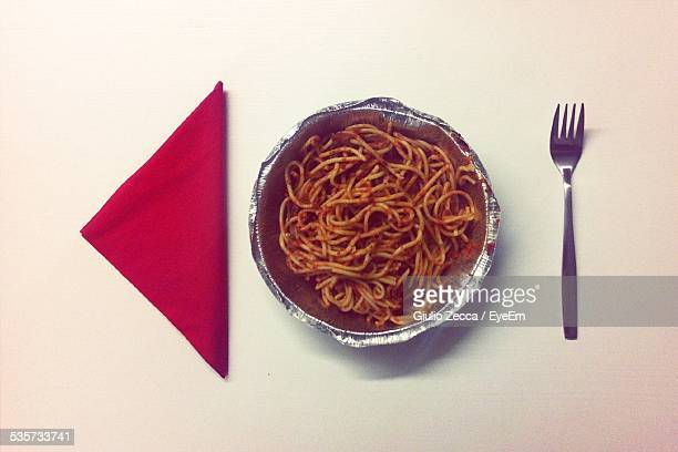 Directly Above Shot Of Spaghetti With Fork And Napkin On White Table