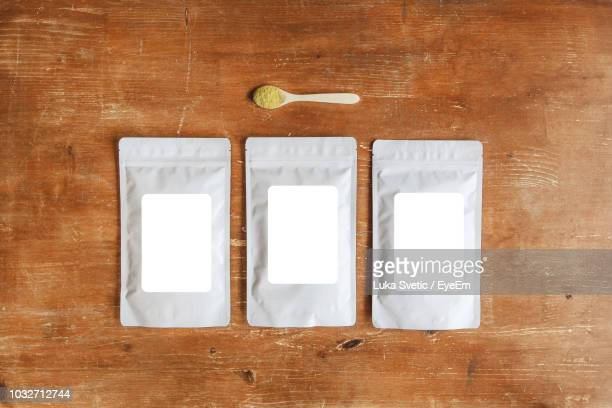 directly above shot of spice packets with wooden spoon on table - packaging stock pictures, royalty-free photos & images
