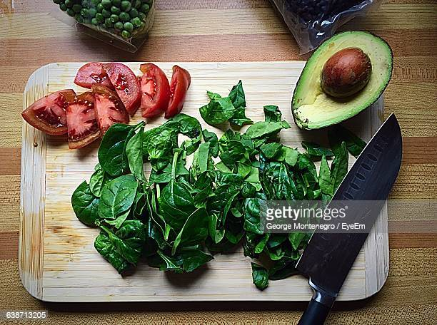 Directly Above Shot Of Spinach With Tomato And Avocado On Cutting Board