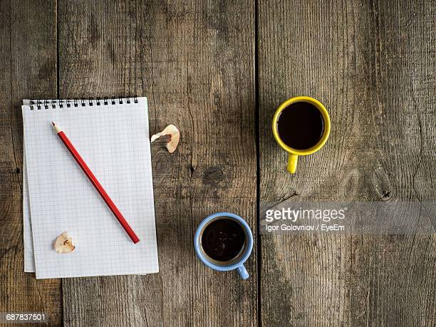 directly above shot of spiral notebook with coffee and pencil on old wooden table - igor golovniov stock pictures, royalty-free photos & images