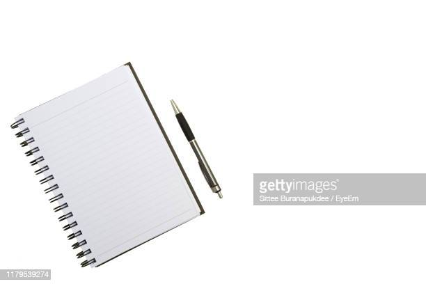 directly above shot of spiral notebook with pen on white background - note pad stock pictures, royalty-free photos & images