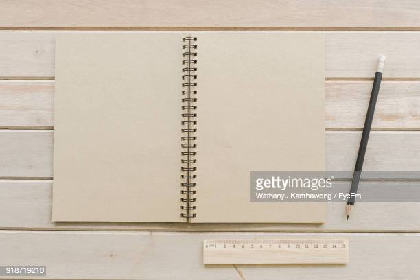 directly above shot of spiral notebook with pencil and ruler on table - spiralblock stock-fotos und bilder