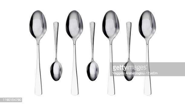 directly above shot of spoons against white background - spoon stock pictures, royalty-free photos & images