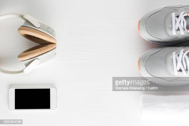 directly above shot of sport shoes with headphones and mobile phone on table - sports shoe stock pictures, royalty-free photos & images