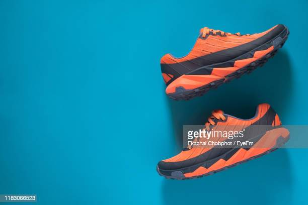 directly above shot of sports shoes against blue background - sports shoe stock pictures, royalty-free photos & images