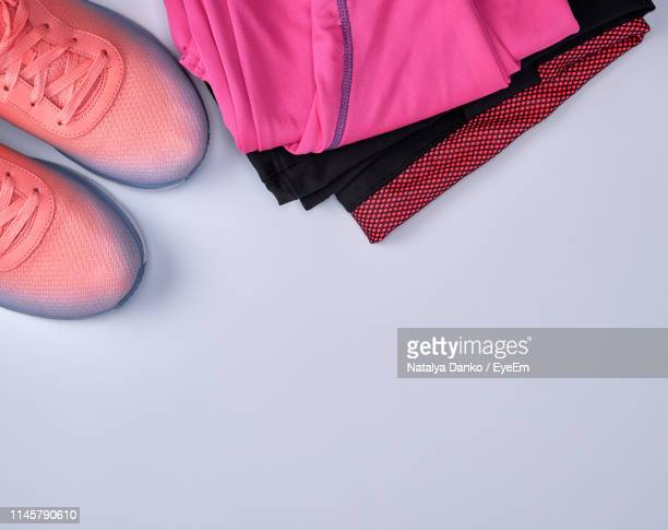 directly above shot of sports shoes with clothing over white background - sports clothing stock pictures, royalty-free photos & images