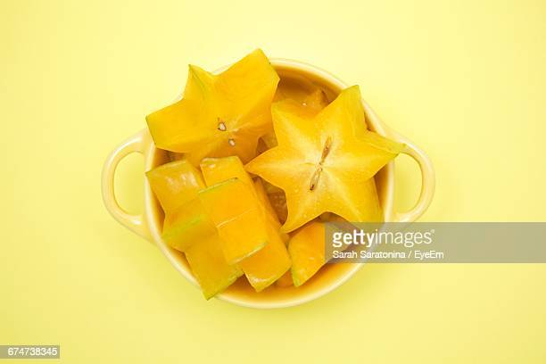 Directly Above Shot Of Starfruits Slices In Bowl On Yellow Table
