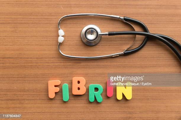 directly above shot of stethoscope with fibrin text on wooden table - fibrin stock pictures, royalty-free photos & images
