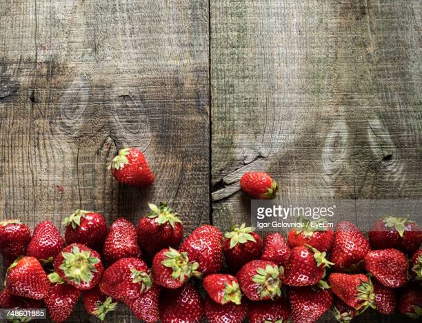 directly above shot of strawberries on wooden table - igor golovniov stock pictures, royalty-free photos & images