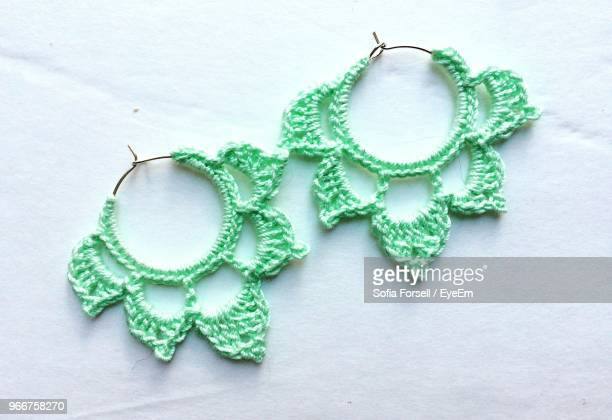 directly above shot of string knitted earrings on table - イヤリング ストックフォトと画像