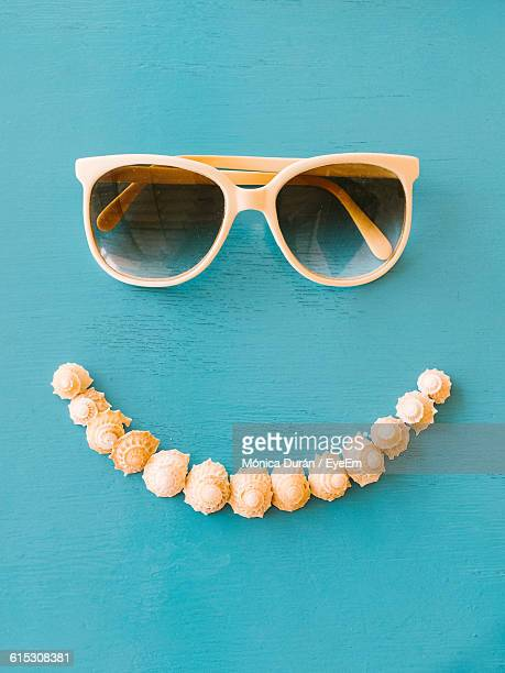 directly above shot of sunglasses and seashells on blue table - nature morte photos et images de collection