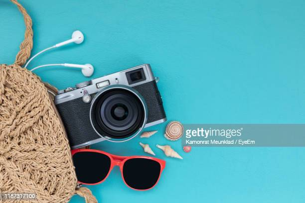 directly above shot of sunglasses with camera and purse on blue background - personal accessory stock pictures, royalty-free photos & images
