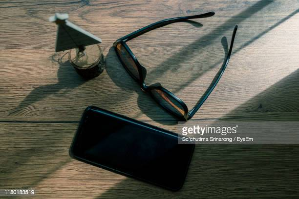 directly above shot of sunglasses with smart phone and christmas model on wooden table - サングラス 無人 ストックフォトと画像