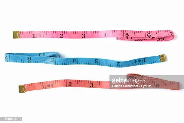 directly above shot of tape measure over white background - tape measure stock pictures, royalty-free photos & images