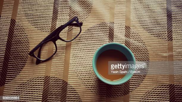 directly above shot of tea and eyeglasses on table - reading glasses stock pictures, royalty-free photos & images