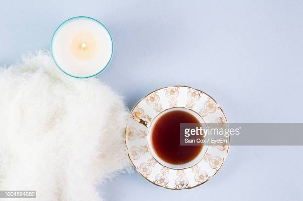 directly above shot of tea by lit tea light candle on table - saucer stock pictures, royalty-free photos & images