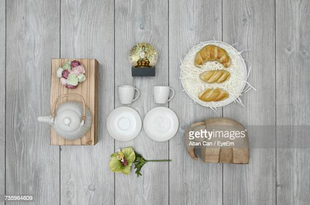 Directly Above Shot Of Tea Set With Croissant Served In Plate On Wooden Table