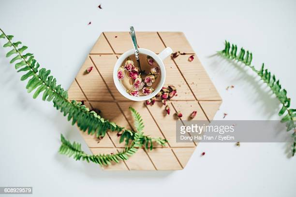 Directly Above Shot Of Tea With Ferns On Hexagon Shape Wood At Table