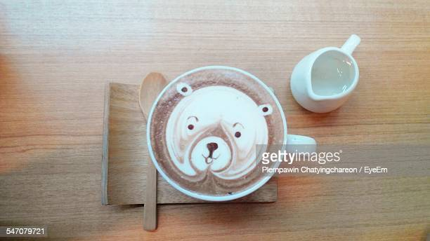 Directly Above Shot Of Teddy Bear Drawn In Coffee On Table