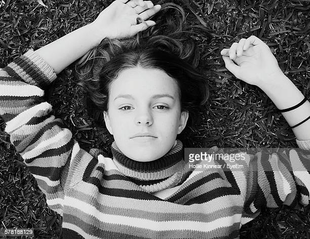 directly above shot of teenage girl lying on grassy field - sólo chicas adolescentes fotografías e imágenes de stock