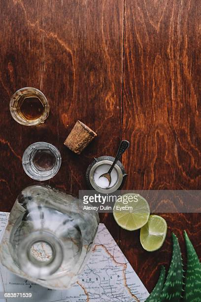 Directly Above Shot Of Tequila And Lemon Slices With Map Paper On Table