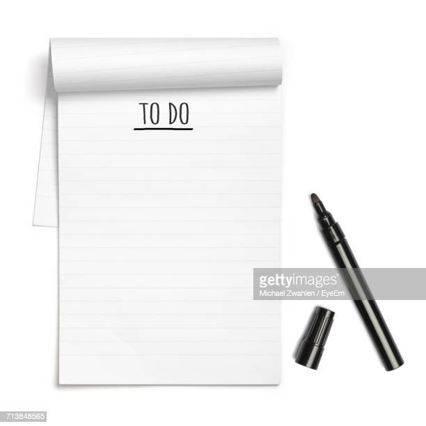directly above shot of text on note pad by felt tip pen over white background - felt tip pen stock pictures, royalty-free photos & images