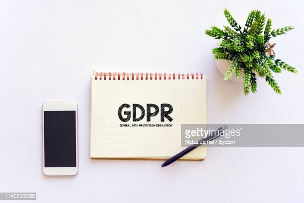 directly above shot of text on spiral notebook with smart phone and plant on gray background - gdpr stock pictures, royalty-free photos & images