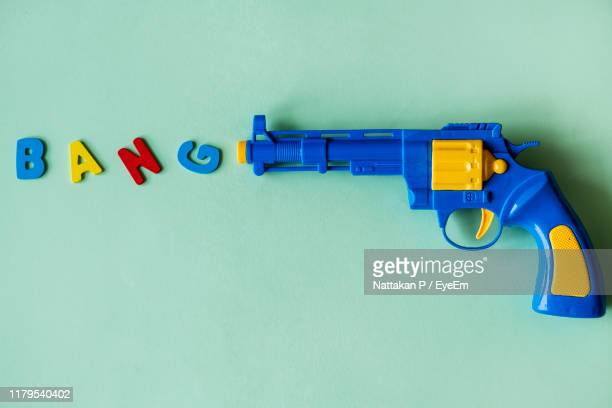 directly above shot of text with toy gun on blue background - pistolet photos et images de collection