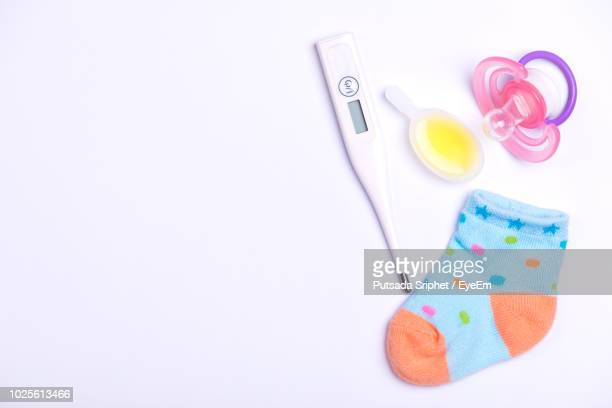 directly above shot of thermometer with baby equipment over white background - mamilo imagens e fotografias de stock