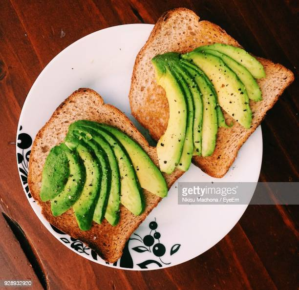 directly above shot of toasted breads with avocados in plate on table - avocado toast stockfoto's en -beelden