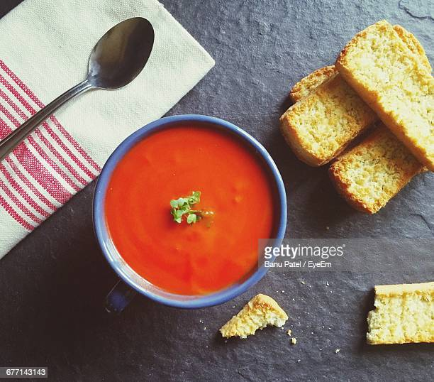 Directly Above Shot Of Tomato Soup With Breads On Table