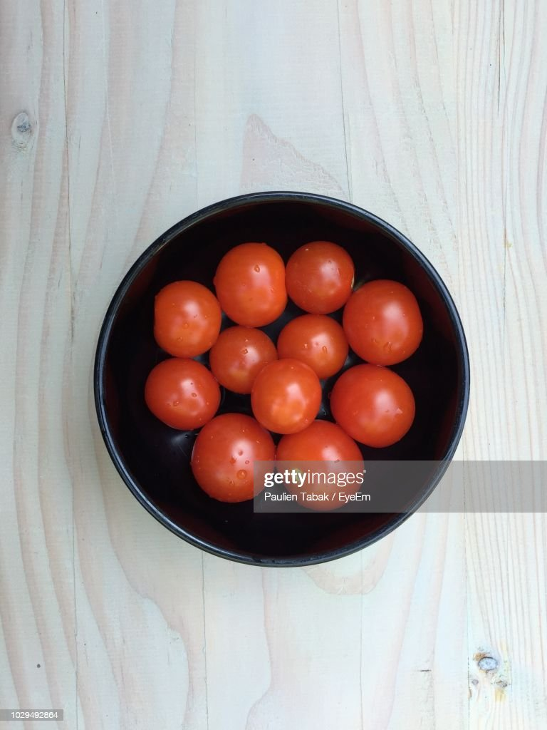 Directly Above Shot Of Tomatoes In Bowl On Wooden Table : Stockfoto