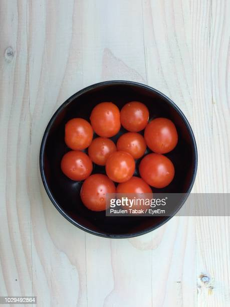 directly above shot of tomatoes in bowl on wooden table - paulien tabak stock pictures, royalty-free photos & images