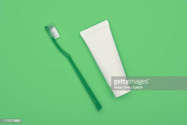 directly above shot of toothpaste and toothbrush over green background - toothbrush stock pictures, royalty-free photos & images