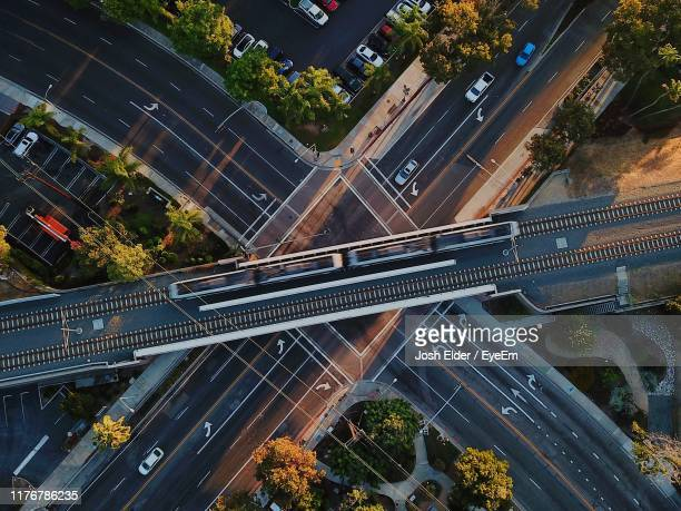directly above shot of train on railway bridge over roads in city - transport stock pictures, royalty-free photos & images