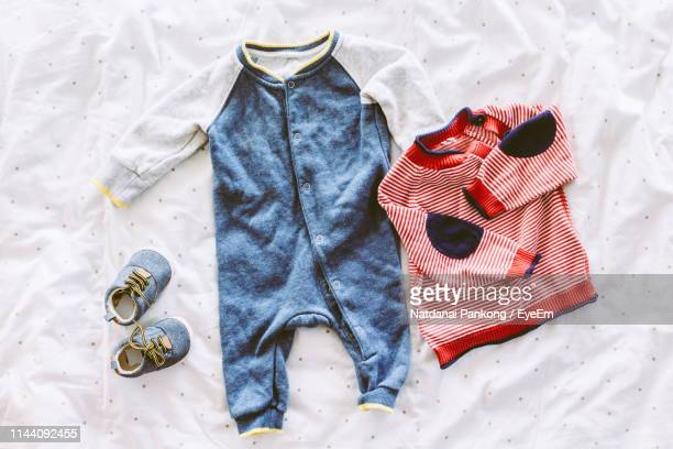 directly above shot of t-shirt on bed - baby clothing stock pictures, royalty-free photos & images