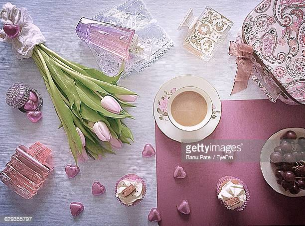Directly Above Shot Of Tulips With Perfumes And Tea On Table