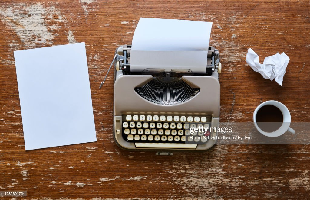Directly Above Shot Of Typewriter And Coffee Cup On Table : Stock Photo