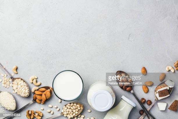 directly above shot of various food and milk over white background - nut food stock pictures, royalty-free photos & images