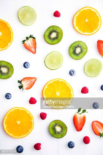 directly above shot of various fruits served on white background - obst stock-fotos und bilder