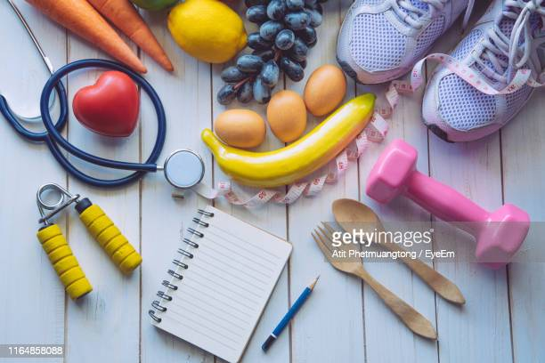 directly above shot of various objects with foods on hardwood floor - stethoscope stock pictures, royalty-free photos & images