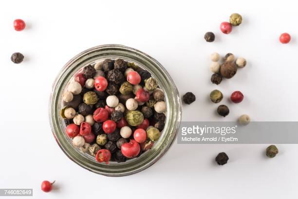 Directly Above Shot Of Various Peppercorns With Jar On White Background