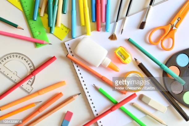 directly above shot of various school supplies on table - schulbedarf stock-fotos und bilder