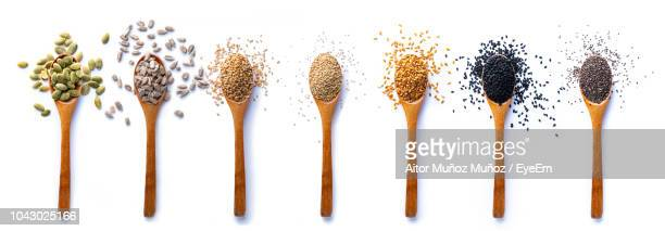 directly above shot of various spices in wooden spoons on white background - spice stock pictures, royalty-free photos & images