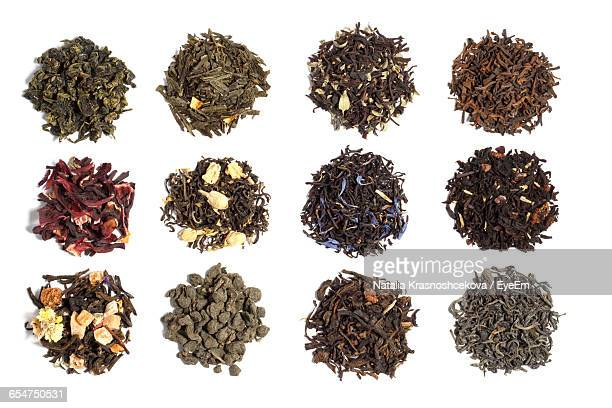 directly above shot of various tea leaves against white background - tea leaves stock photos and pictures