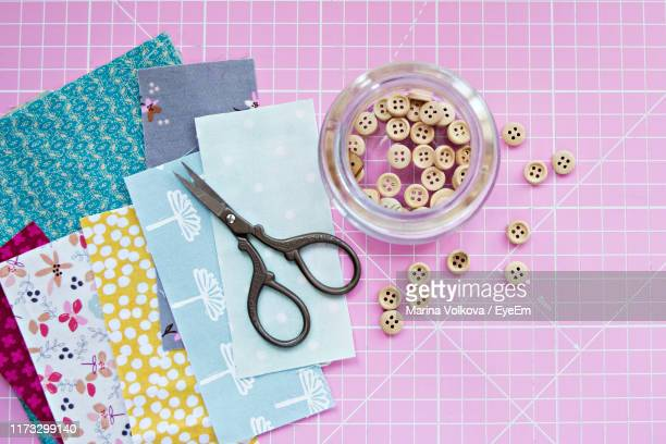 directly above shot of various textiles and sewing item on pink table - button sewing item stock pictures, royalty-free photos & images