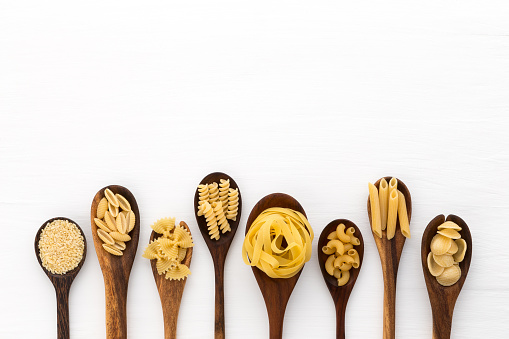 Directly Above Shot Of Various Uncooked Pastas In Wooden Spoons Over White Background - gettyimageskorea