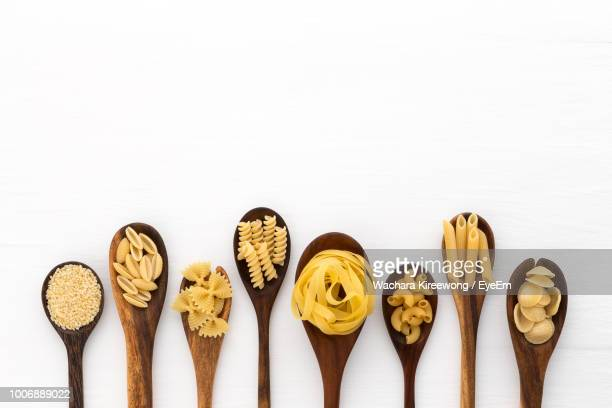 directly above shot of various uncooked pastas in wooden spoons over white background - pasta stock pictures, royalty-free photos & images