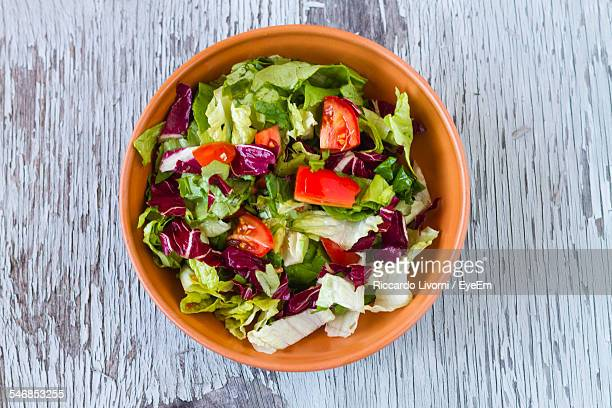 directly above shot of vegetable salad in bowl on wooden table - salad ストックフォトと画像